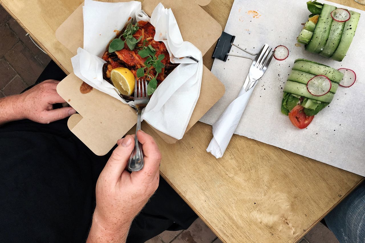 Cropped image of person having lunch at table