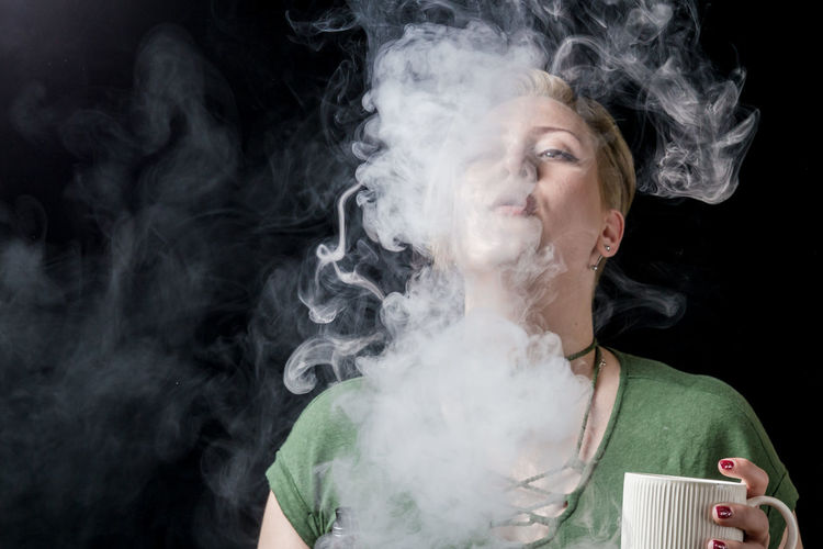 Close-Up Of Woman Smoking Against Black Background