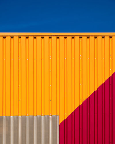 Multi colored cargo container against blue sky
