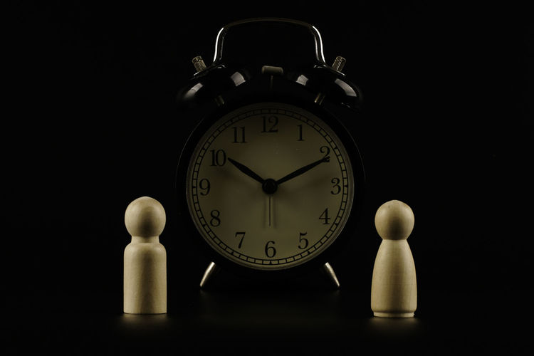 Close-up of clock on table against black background