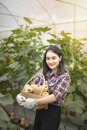 Portrait of smiling young woman carrying vegetables while standing against plants in greenhouse