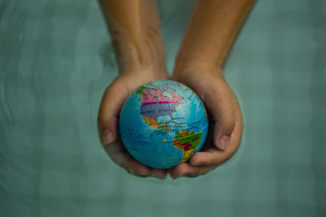 Above close up looking down on hands holding the world over water Atlantic Ocean Hand Holding Hands Immigration Map Plant Power USA America Canada Cat Citizen Of The World Citizenship Continent Ecology Energy Ocean Planet Protection South America Sustainability Sustainable Sustainable Resources Water World