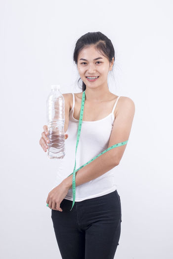 Cold Drink Dieting Drink Drinking Drinking Glass Drinking Water Exercising Food And Drink Happiness Healthy Eating Healthy Lifestyle Holding Lifestyles Looking At Camera One Person Portrait Purified Water Refreshment Smiling Standing Studio Shot Water Water Bottle  White Background Young Adult