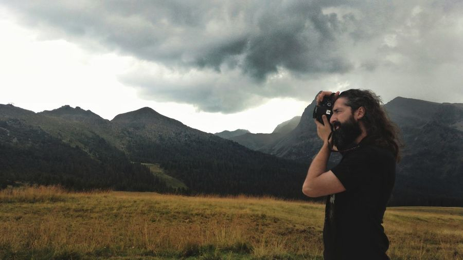 Side view of man photographing on mountain against cloudy sky