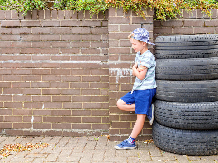 Day view cute little child boy posing next to stack of used tyres over brick english wall Cool Tires Boy Brick Casual Clothing Child Childhood Day Full Length Innocence Leisure Activity Lifestyles Looking Offspring One Person Outdoors Posing Real People Shorts Side View Standing Tyres