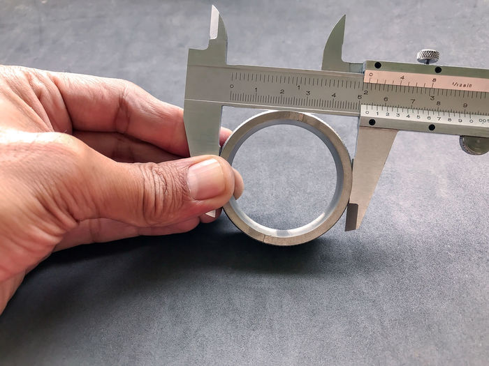 Cropped Hand Measuring Hole With Ruler