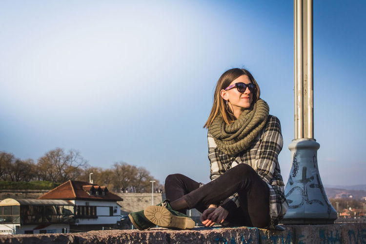 Portrait of smiling young woman sitting against built structure against clear sky