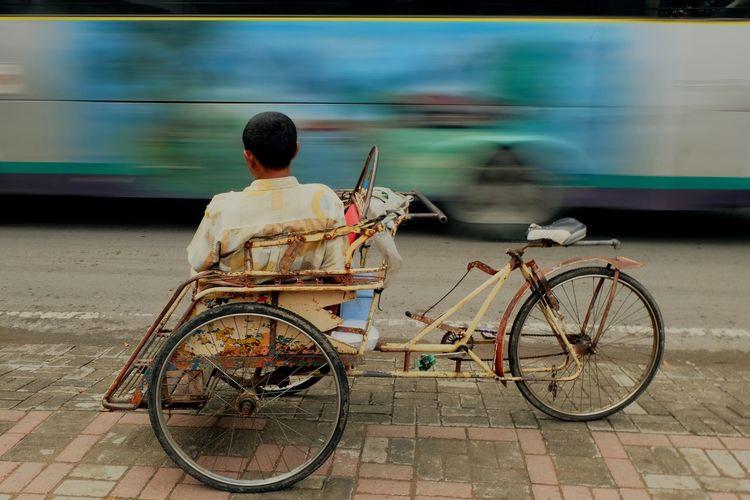 Rear view of man sitting on pedicab