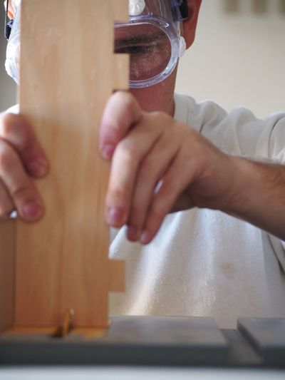Close-Up Of Carpenter Working With Wooden Plank At Desk