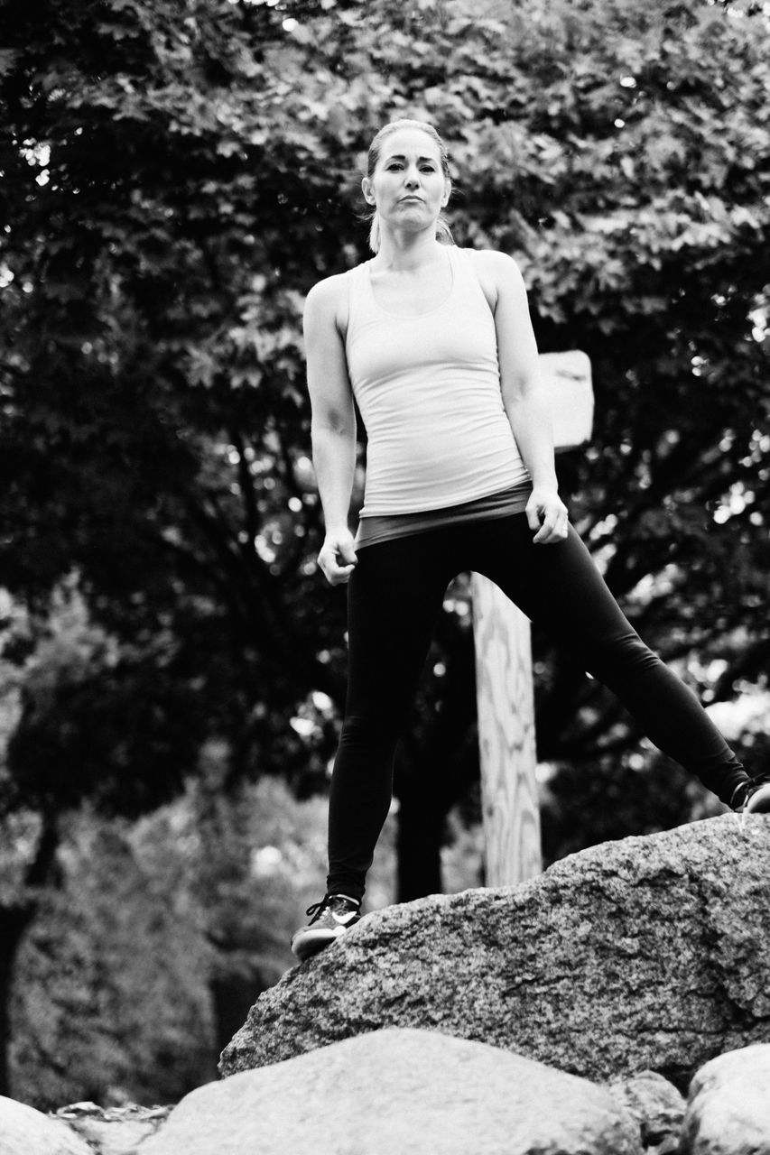 rock - object, real people, young adult, young women, lifestyles, one person, day, outdoors, full length, exercising, leisure activity, sports clothing, tree, healthy lifestyle, beautiful woman, smiling, nature, people