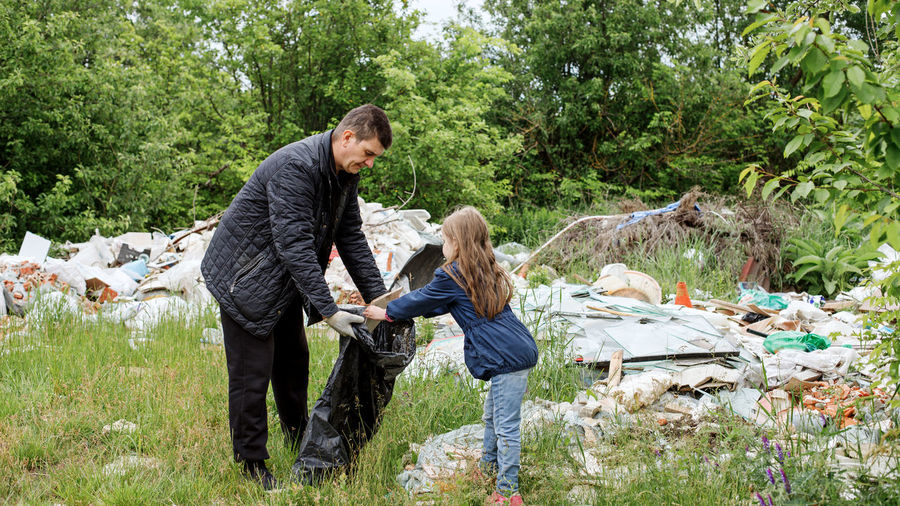Full length of father and daughter collecting garbage outdoors