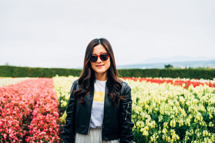 One Person Smiling Flower Young Adult Plant Sunglasses Glasses Portrait Flowering Plant Standing Nature Long Hair Hairstyle Hair Front View Adult Land Field Happiness Fashion Beautiful Woman Outdoors