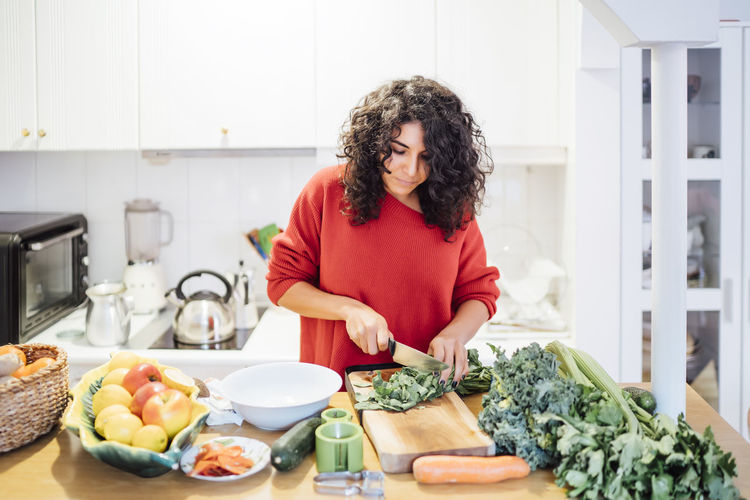 Young woman standing by food at home