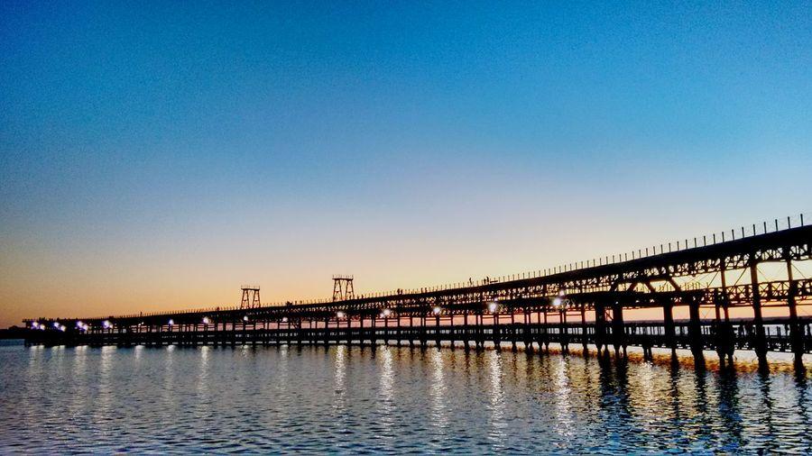 Bridge over calm river against clear sky at dusk