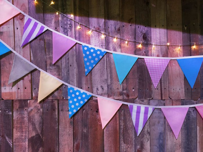 Various Patterned Triangular Flags on Wooden Planks Background Bunting Cable Close-up Curved  Day Decorative Flag Lighting Multi Colored No People Party Pattern Plank Striped Wooden
