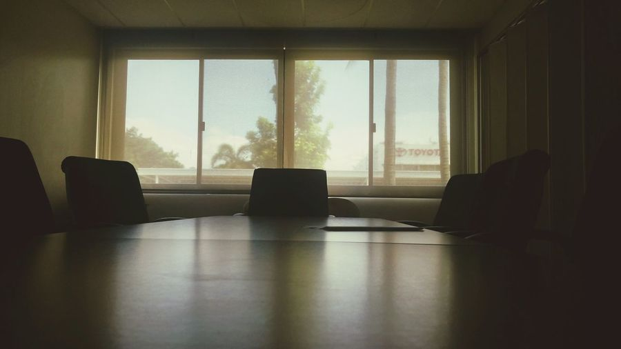 Empty chairs and table against window in board room