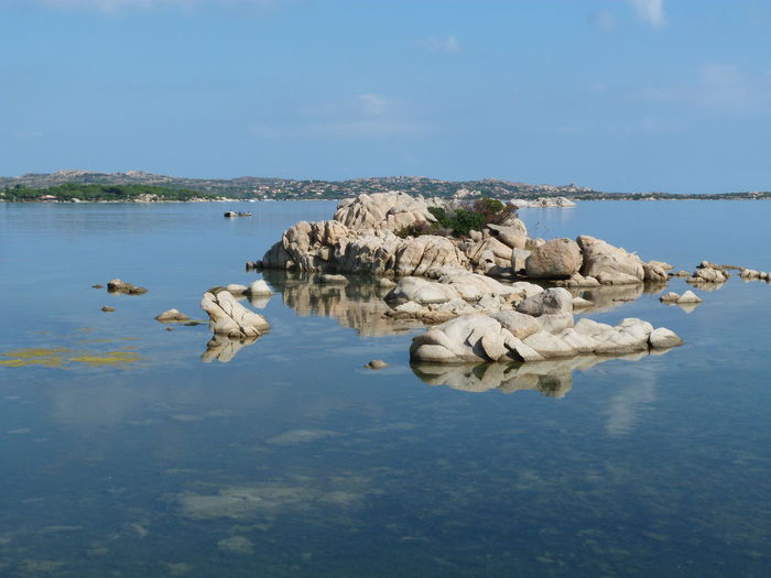 Rocks in lake against blue sky