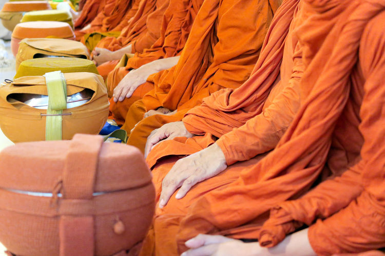 Midsection of monks sitting with containers at temple
