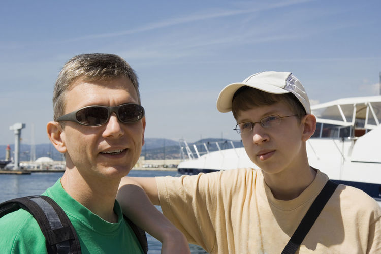 Father and son standing at harbor on sunny day against sky
