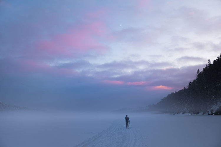 Skiing on a frozen, misty new moon is seen behind coloured evening Norway. A New Beginning EyeEmNewHere Norway Oslo Peace Wilderness Forest Rectration Skiing Lifestyles Moon Twilight Evening Beautiful Tranquil Scene Cloud - Sky Sky Outdoors Environment Real People Tranquility Nature One Person Winter Snow