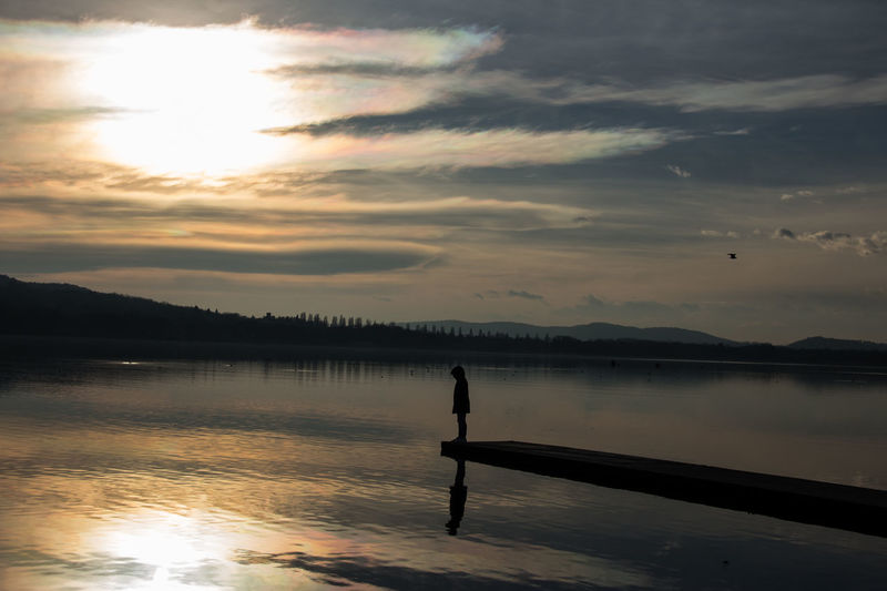Silhouette man standing in lake against sky during sunset