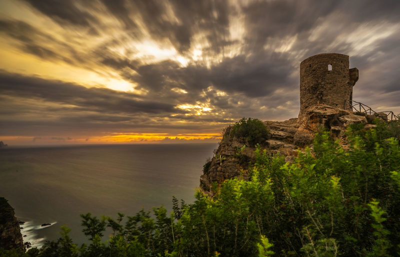 Old ruin building against cloudy sky during sunset