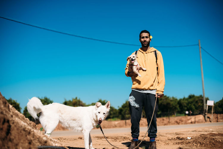 Man with dog standing against sky