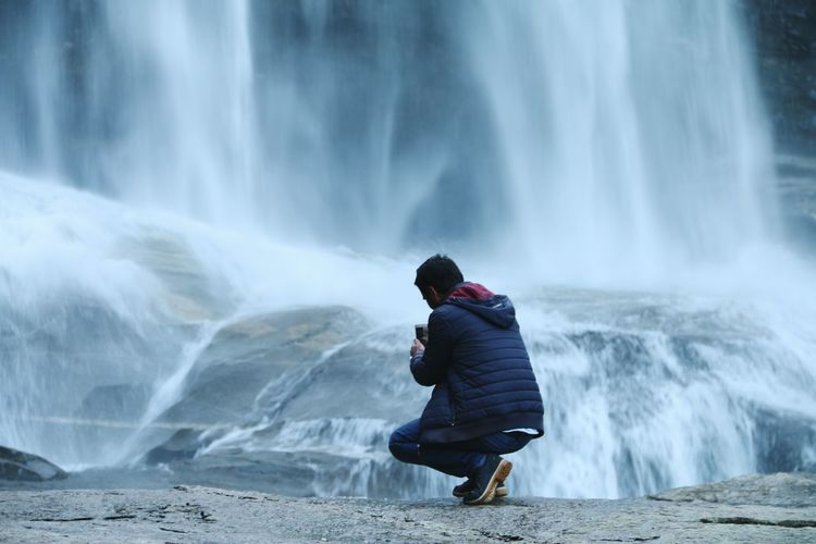 Rear view of man photographing waterfall