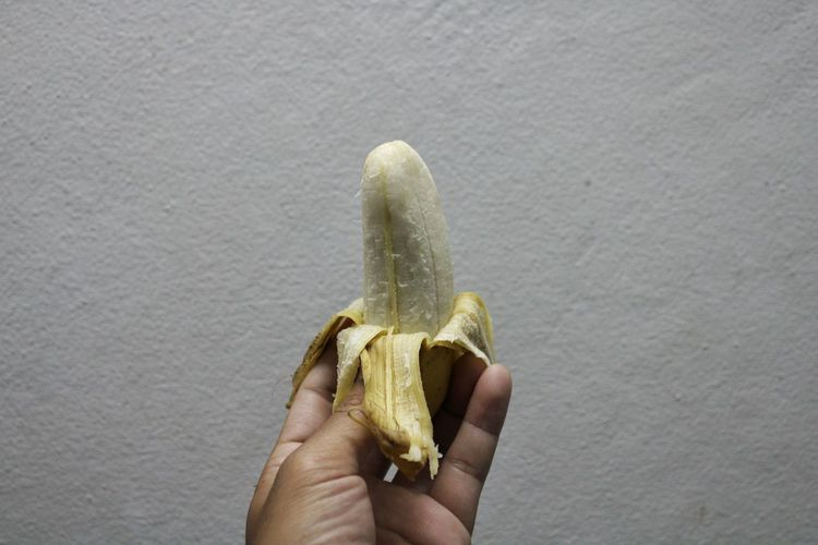 Peeled banana on a hand