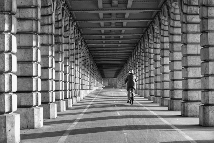 Rear View Of Person Riding Bicycle On Road Amidst Colonnades