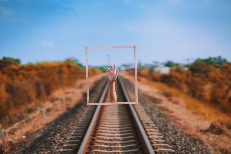 Digital composite image of hand over railroad track against sky