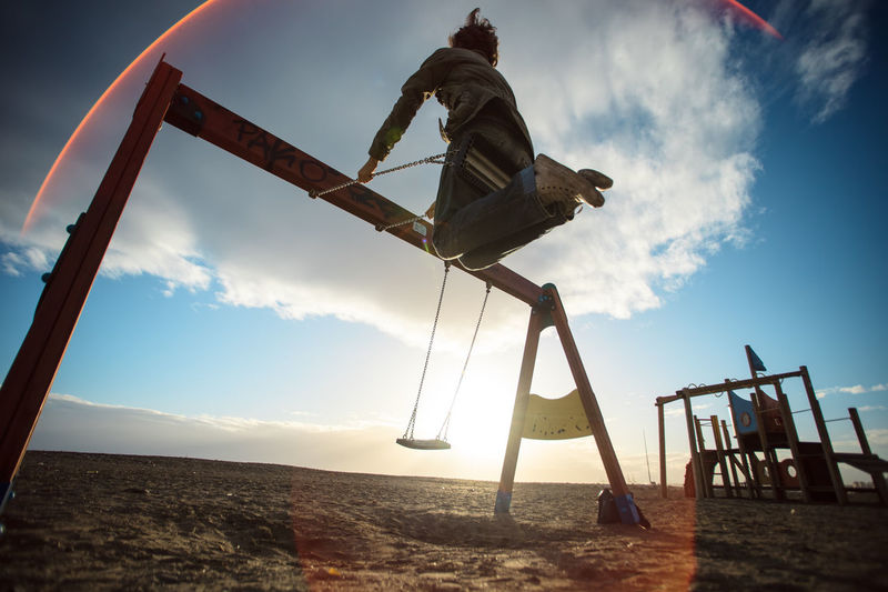 Low angle view of woman swinging at playground against sky during sunset