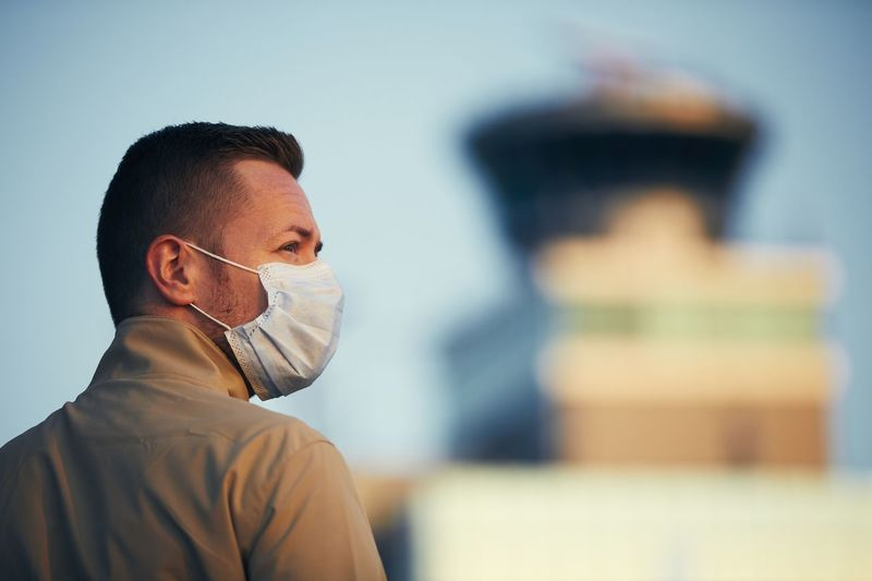 Close-up of man wearing mask standing against building outdoors