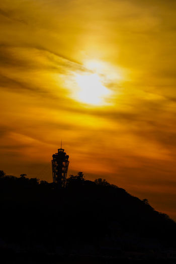 Low angle view of silhouette tower against sky during sunset