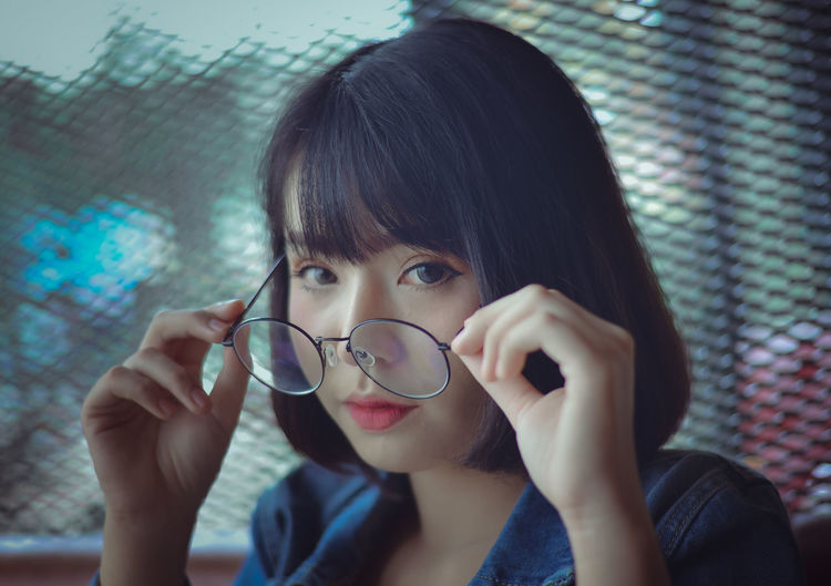 Close-Up Portrait Of Young Woman Wearing Eyeglasses Against Window