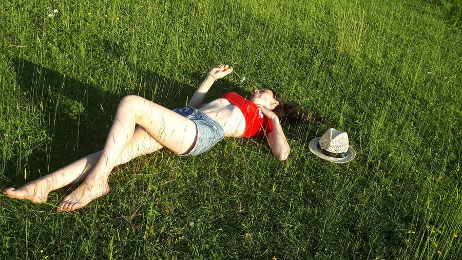 High Angle View Of Young Woman Lying On Land