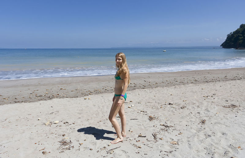 Young woman wearing bikini standing on sea shore at beach against blue sky