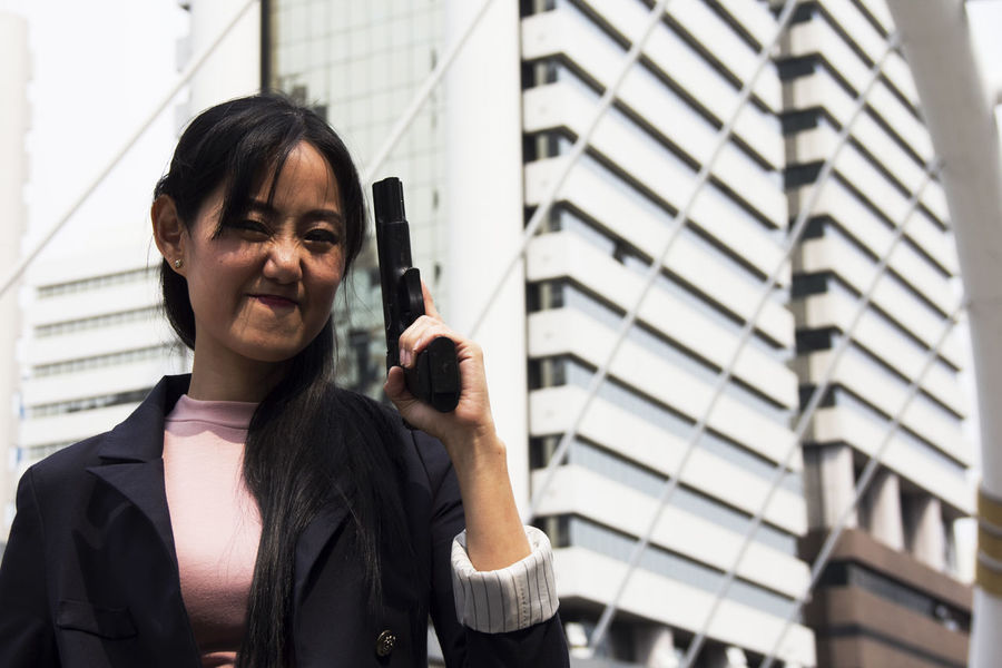 Beautiful Asia girl close up. Gun Gun Range Architecture Black Hair Close-up Day Focus On Foreground Front View Gun Control Headshot Holding Indoors  Leisure Activity Lifestyles Low Angle View One Person Real People Standing Young Adult Young Women
