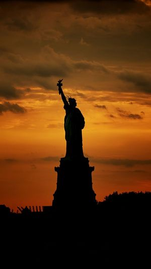 Silhouette of statue against cloudy sky during sunset