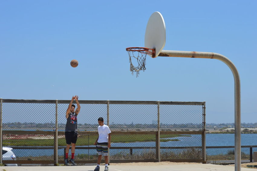 Ball Basketball - Sport Basketball Hoop Basketball Player Beach Volleyball Court Day Leisure Activity Lifestyles Men Mid-air Motion Net - Sports Equipment Outdoors Playing Practicing Real People Sky Soccer Sport Sportsman Taking A Shot - Sport Team Sport Two People Volleyball - Sport