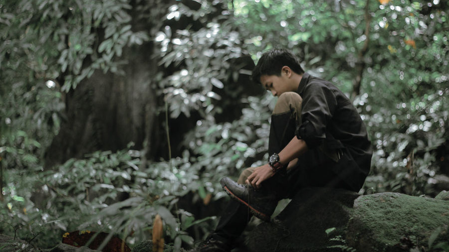 Side view of teenage boy holding plant in forest