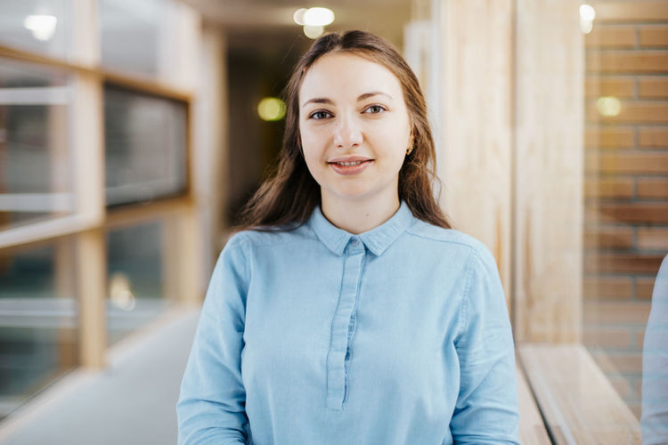 smiling caucasian businesswoman wearing a blue blouse Portrait Looking At Camera Smiling Focus On Foreground Front View One Person Young Adult Indoors  Confidence  Standing Waist Up Women Beautiful Woman Young Women Emotion Casual Clothing Architecture Adult Real People Hairstyle Teenager Businesswoman Confidence  Confident  Caucasian