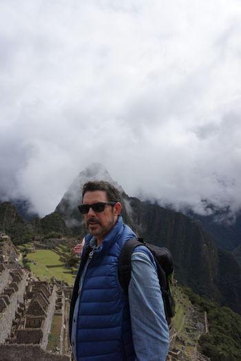 Man standing by machu picchu against cloudy sky