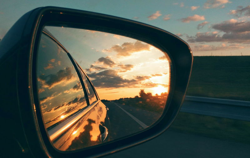 Reflection of car on side-view mirror during sunset