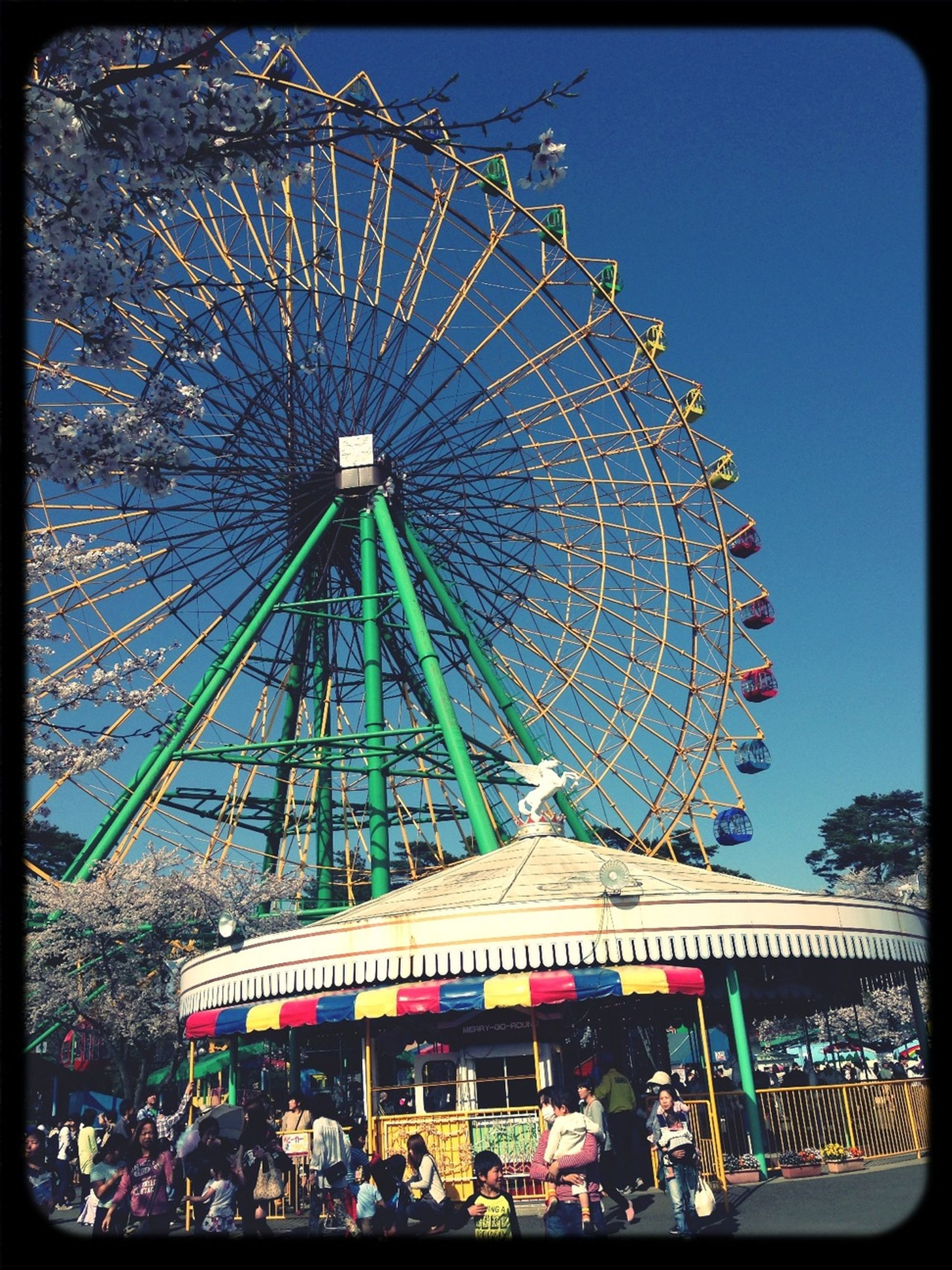 amusement park, amusement park ride, ferris wheel, arts culture and entertainment, clear sky, low angle view, transfer print, built structure, fun, blue, auto post production filter, architecture, metal, sky, enjoyment, outdoors, traveling carnival, day, circle, leisure activity