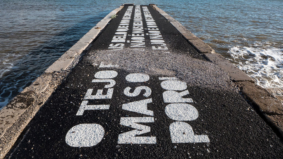 High angle view of text on road by sea