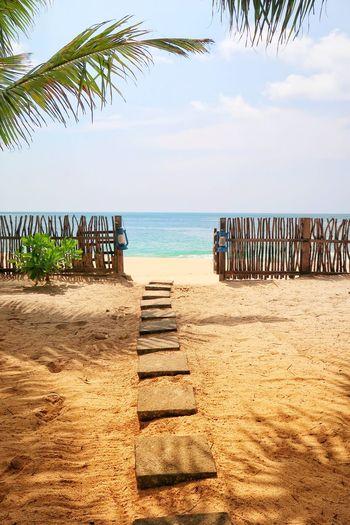 Boardwalk leading towards sea at beach against sky