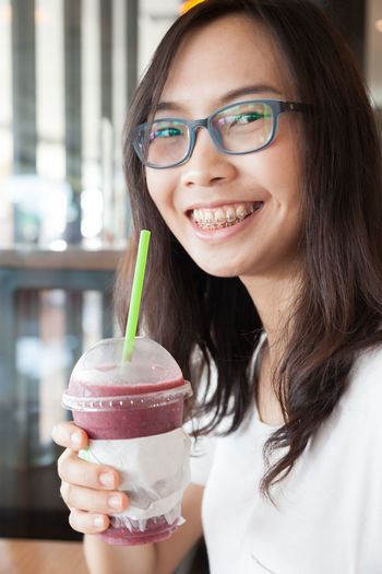 Close-Up Portrait Of Smiling Young Woman Holding Drink