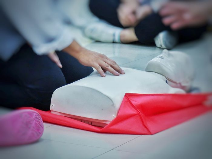 Midsection of person with cpr dummy during training