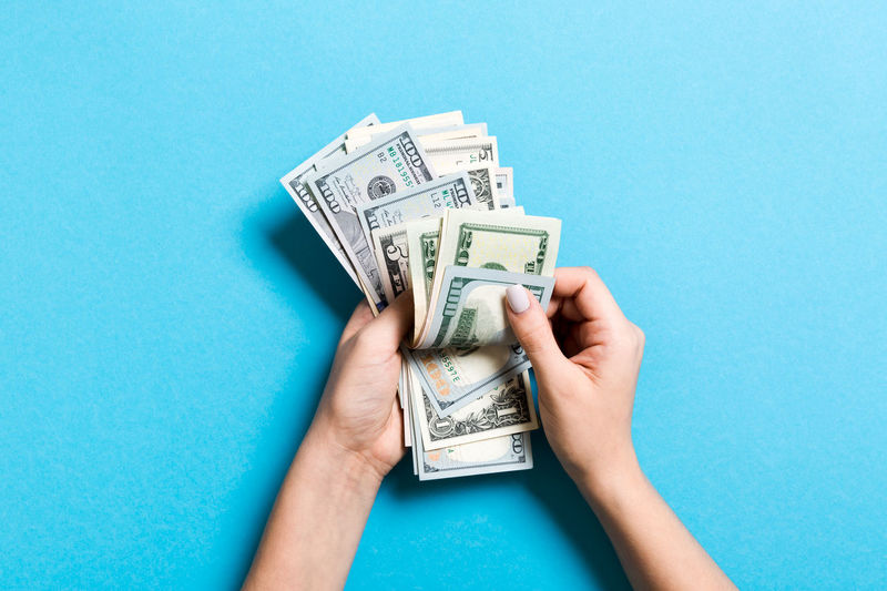 Close-up of hands holding paper currency against blue background